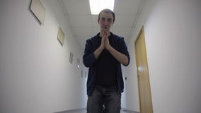 Young man prays kneeling in white hallway stock footage
