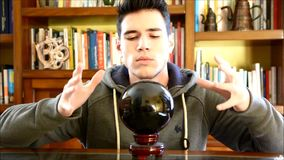 Young man predicting the future by looking in crystal ball stock video footage