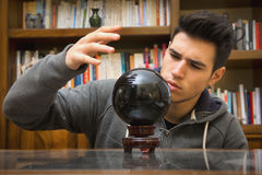 Young man predicting the future by looking into. Handsome young male soothsayer predicting the future by looking into black crystal ball Royalty Free Stock Photos