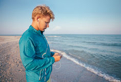 Young man prepared his musical device before run training Royalty Free Stock Images