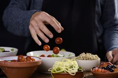 Young man preparing a buddha bowl. Closeup of a young caucasian man preparing a buddha bowl, with different ingredients, such as lettuce, cornsalad, quinoa royalty free stock photos