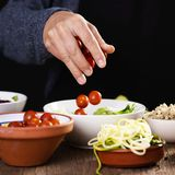 Young man preparing a buddha bowl salad. Closeup of a young caucasian man preparing a buddha bowl salad, with different ingredients, such as lettuce, cornsalad stock photo