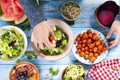 Young man preparing a buddha bowl salad. High angle view of a caucasian man preparing a buddha bowl salad, with different ingredients, such as lettuce, cornsalad royalty free stock photos