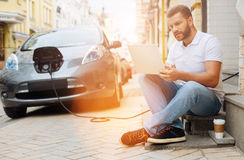 Young man preparing for business meeting while waiting. Using time rationally. Handsome young man sitting on the steps and studying materials on a laptop Royalty Free Stock Images