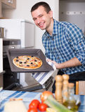 Young man preparing delicious pizza in oven. Young happy man preparing delicious pizza in oven in kitchen at home Stock Image