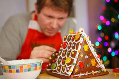 Young man preparing a gingerbread cookie house Royalty Free Stock Photography