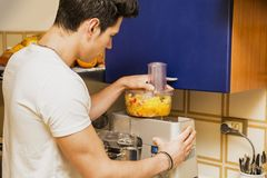Young man preparing healthy fruit smoothie Royalty Free Stock Image
