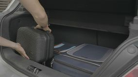 Young man preparing his travel bags inside the trunk of car ready for vacation - stock footage