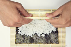 Young man preparing makizushi Royalty Free Stock Image
