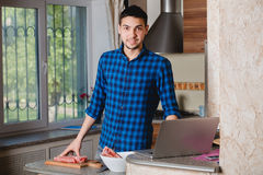 Young man preparing meat in her kitchen , looking into the frame Stock Image