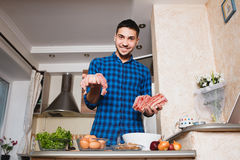 Young man preparing meat in her kitchen , looking into the frame Stock Photo