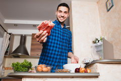 Young man preparing meat in her kitchen , looking into the frame Stock Photos