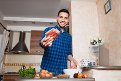 Young man preparing meat in her kitchen , looking into the frame Royalty Free Stock Image