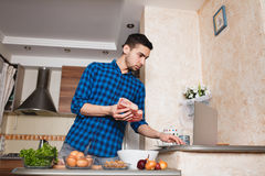 Young man preparing meat in her kitchen , looking into the frame Royalty Free Stock Photos