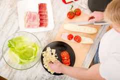 Young man preparing a Sandwich Stock Images