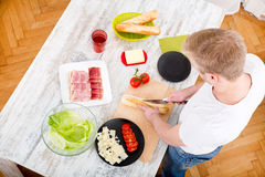 Young man preparing a Sandwich Stock Image