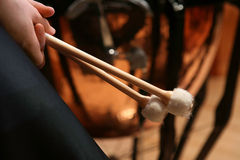 Young Man Preparing to Play Bass Drum. Young man holds the sticks before playing bass drum Royalty Free Stock Images