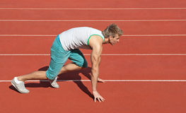 Young man preparing to run. Young man on a racetrack preparing to run stock images