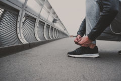Young man preparing to run in the city, tying jogging shoes Stock Images