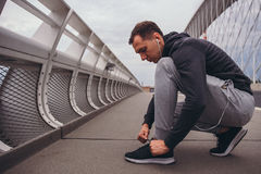 Young man preparing to run in the city, tying jogging shoes Royalty Free Stock Images