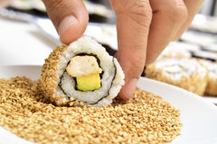 Young man preparing uramaki Royalty Free Stock Images
