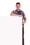 Young man presenting on banner. Casual young man presenting something on a blank banner and smiling Stock Photo