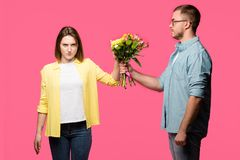 young man presenting bouquet of flowers to angry woman isolated