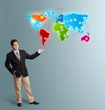Young man presenting colorful world map Royalty Free Stock Images
