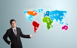 Young man presenting colorful world map Royalty Free Stock Photos
