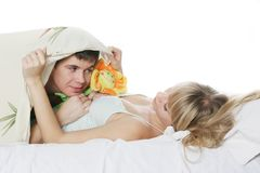 Young man presenting toy flower to girl in bed Stock Images