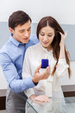 Young man presents engagement ring to his woman. Young men presents engagement ring to his women at jeweler's shop. Concept of wealth and luxurious life stock photo
