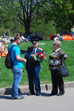 Young man presents flowers to a war veteran. Stock Photos