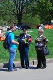 Young man presents flowers to a war veteran. Stock Photos