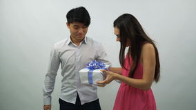 Young man presents gift box to girl on a white background stock footage