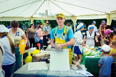 Young man presents plastering skills. Zaporizhia/Ukraine- June 5, 2016: smiling young man volunteer presents plastering skills on charity family festival Royalty Free Stock Photo