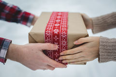 Young man presents women Christmas gift in the forest Stock Photography