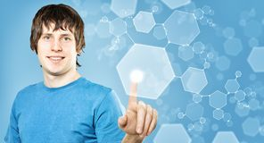 Young Man Press Button on Blue Background Stock Photos