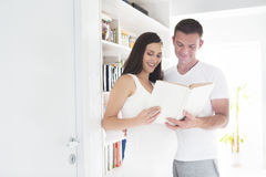 Young man and pretty pregnant woman reading book indoors. Young men and pretty pregnant women reading book indoors. Pregnancy and family concept Stock Images