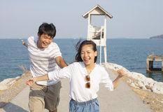 Young man and pretty woman joyful emotion and playing at sea sid Stock Photography