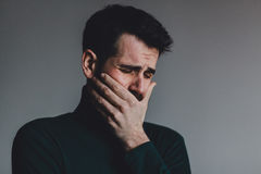 Young man with a problem crying. Studio shot Royalty Free Stock Photo