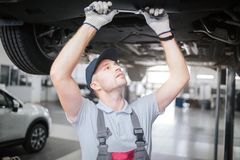 Young man in process of working underneath car. He looks up to right and hold big wrench with both hands. He is royalty free stock photography