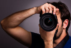 Young man with professional camera. Isolated on gray background Royalty Free Stock Photo