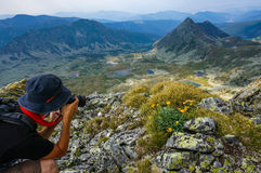 Young man with professional camera photographing the beautiful landscape Stock Images
