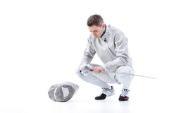 Young man professional fencer holding sword and crouching Royalty Free Stock Photos