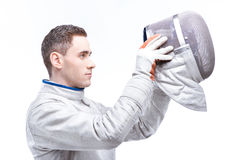 Young man professional fencer wearing helmet on white Royalty Free Stock Photography