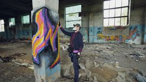 Young man professional graffiti painter is working inside abandoned building, he is painting with spray aerosol paint on. Young man professional graffiti painter stock video