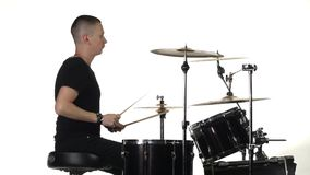 Young man professionally plays percussion instruments . White background. Side view. Young man sitting on a chair beautifully and professionally vigorously plays stock video