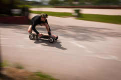 Riding fast on an electric skateboard Stock Images