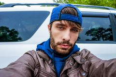 A young man with a prominent beard poses for a selfie looking directly into the camera`s lens wearing a bright navy blue hat and s stock photo