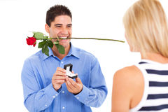 Young man proposing. Young men with rose and ring proposing to his girlfriend Stock Image